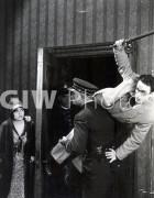 Welcome to Danger -  Harold Lloyd on cop's shoulder in doorway, with girl