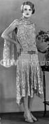 A model wearing a long patterned dress showing the popular uneven hemline in 1929
