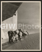 Arizona-Nevada border. late 1930s or early 1940s. Three construction workers putting a coat of paint on a slanted wall