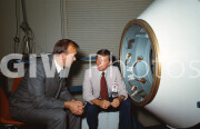 Two senior flight directors confer outside a mockup of the ASTP docking module. At left is Soviet flight director Alexei