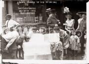 New York City. 1910s. Licking blocks of ice on hot day.